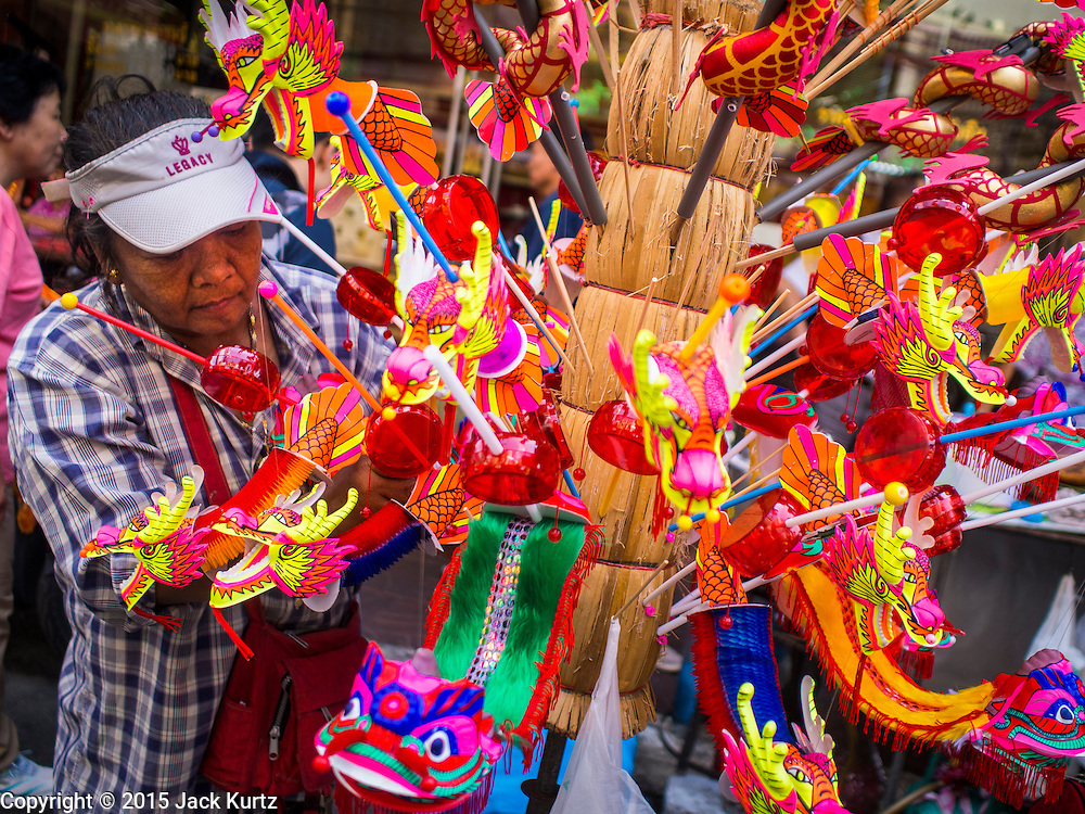 """17 FEBRUARY 2015 - BANGKOK, THAILAND: A vendor sells Chinese New Year toys in Bangkok's Chinatown district. Chinese New Year is February 19 in 2015. It marks the beginning of the Year of Sheep. The Sheep is the eighth sign in Chinese astrology and the number """"8"""" is considered to be a very lucky number. It symbolizes wisdom, fortune and prosperity. Ethnic Chinese make up nearly 15% of the Thai population. Chinese New Year (also called Tet or Lunar New Year) is widely celebrated in Thailand, especially in urban areas like Bangkok, Chiang Mai and Hat Yai that have large Chinese populations.       PHOTO BY JACK KURTZ"""