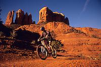 A mountain biker rides a trail below Cathedral Roack in Sedona, Arizona.