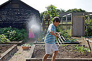 Charlotte, 6 and Joseph, 12, playing with the water in the vegetable garden at Hares Farm CREDIT: Vanessa Berberian for The Wall Street Journal<br /> UKFARM-Hares Farm