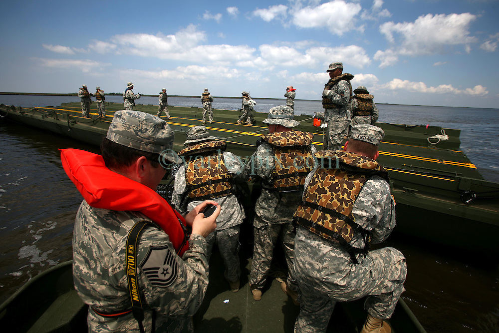 06 May 2010. Shell Beach, Louisiana. Deepwater Horizon, British Petroleum environmental oil spill disaster.<br /> Soldiers from the 2225th Multi-Role Bridge Company Louisiana National Guard commence work on a floating pontoon which will be used by local fishermen to load oil containment boom. With oil reaching ever closer to the St Bernard Parish wetlands, it is vitally important to get more oil containment booms in place.<br /> Photo credit;Charlie Varley/varleypix.com