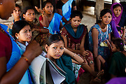 Sita Tharu (center in turquoise), 14, is six months pregnant as she gathers with other child mothers and child brides to see Pahari Tharu, 52, the female community health worker in Bhaishahi village, Bardia, Western Nepal, on 29th June 2012. Sita eloped and married last year at 13 and is now 6 months pregnant. In Bardia, StC works with the district health office to build the capacity of female community health workers who are on the frontline of health service provision like ante-natal and post-natal care, and working together against child marriage and teenage pregnancy especially in rural areas. Photo by Suzanne Lee for Save The Children UK