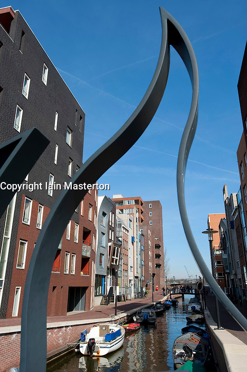 View from ornate footbridge of modern apartment buildings and canal in Java Island district of Amsterdam The Netherlands