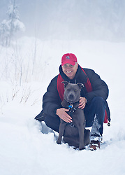 good looking mature man with his dog in the snow