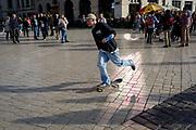 A skateboarder pushes off through reflected light outside the Church of St Mary on Rynek Glowny market square, on 22nd September 2019, in Krakow, Malopolska, Poland.