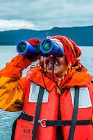 Elderly passenger looking at wildlife through binoculars on a skiff excursion from the Wilderness Explorer, Patterson Bay, Chichagof Island, Inside Passage, Southeast Alaska USA.
