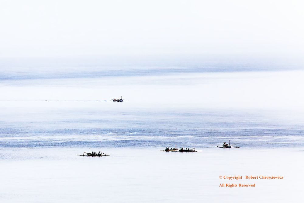 """Bunudan Fishing: The unusually strong glare on a calm ocean gives the water an """"ice-like"""" or minimalist quality, as fishermen take to seas in their hand crafted vessels, Bunudan (near Amed) - Bali Indonesia."""