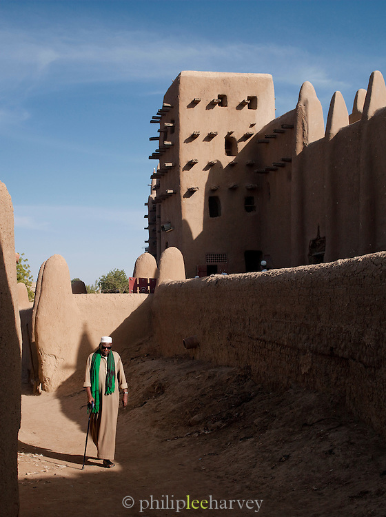 A man walks beside the Great Mosque of Djenné, the worlds largest mud built structure and UNESCO heritage site, at Djenné, Mali