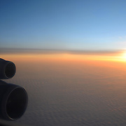 Sunset clouds from the plane with the detail of plane wing, fuselage and engines