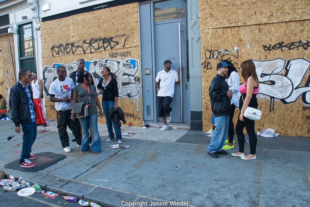 Youth messing around in street of boarded up shop fronts.