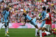 Vincent Kompany of Manchester city stretches for a header over Olivier Giroud of Arsenal (on ground). The Emirates FA Cup semi-final match, Arsenal v Manchester city at Wembley Stadium in London on Sunday 23rd April 2017.<br /> pic by Andrew Orchard,  Andrew Orchard sports photography.