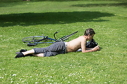 © Licensed to London News Pictures. 12/05/2016. LONDON, UK.  A cyclist relaxes on the grass during warm sunny weather in Green Park at lunchtime.  Photo credit: Vickie Flores/LNP