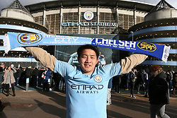 A Manchester City supporter poses with a Mancester City and Chelsea scarf