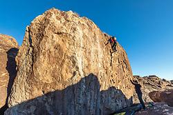 Climber climbing large cliff face, Hueco Tanks State Park & Historic Site, El Paso, Texas. USA.
