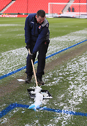 A member of ground staff clears the snow from the pitch ahead of the Premier League match at the bet365 Stadium, Stoke.