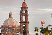A hot air balloon floats past the spire of San Francisco church and the dome of the Las Monjas Church in the historic center of San Miguel de Allende, Mexico.