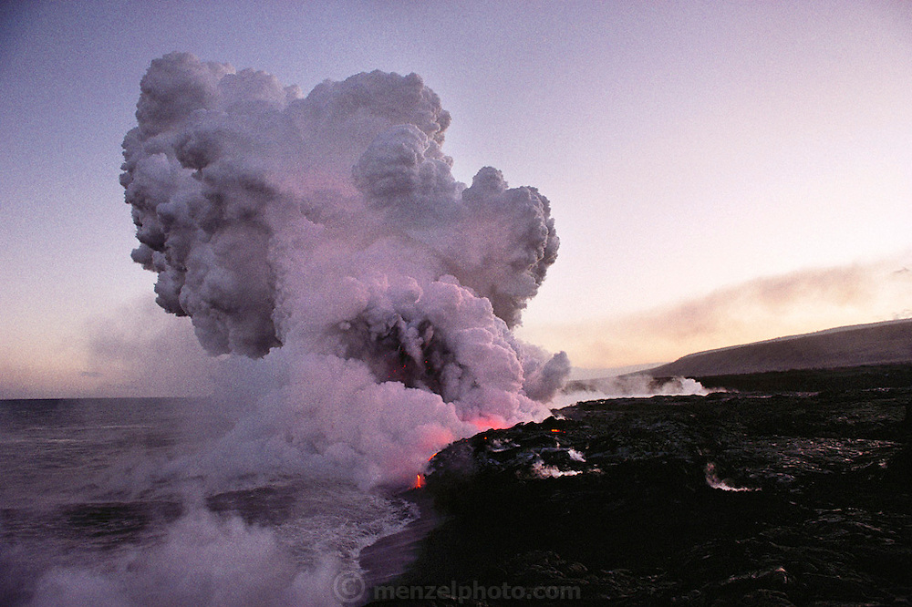 A steam cloud rises above lava flowing into the sea from the Kilauea eruption. Volcano National Park, Big Island, Hawaii. USA.