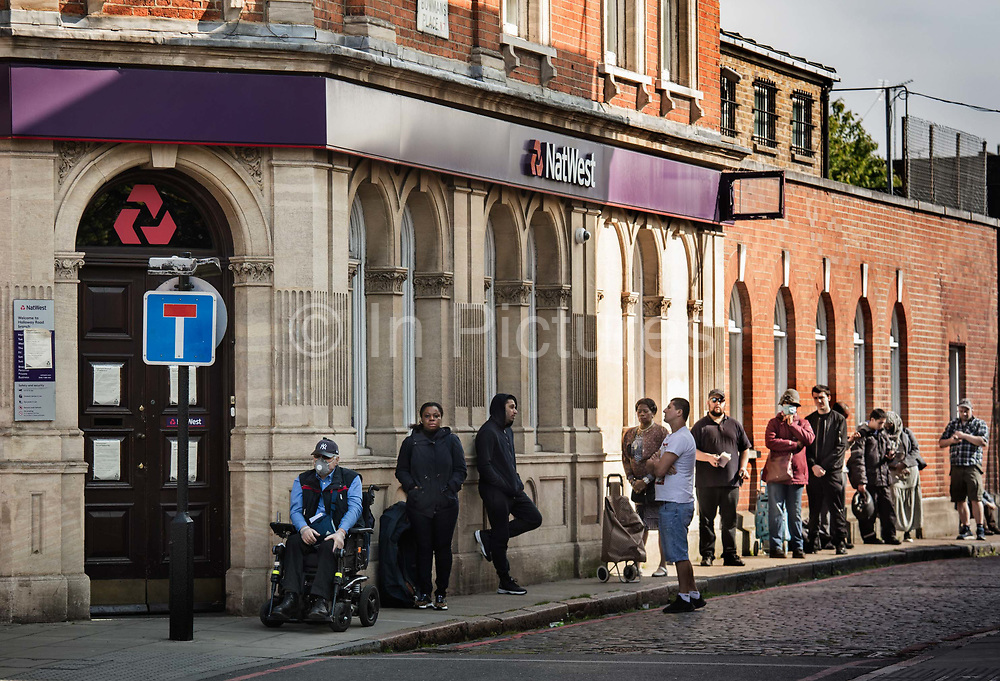 Queue of people waiting for the bank to open at 9.30am on the Holloway Road during the coronavirus pandemic on the 24th April 2020 in London, United Kingdom. Only two customers are allowed in a NatWest branch at a time and once inside, people are asked to stand in marked areas on the floor to make sure they are social distancing. <br /> Britains banking sector scrapped billions of pounds in shareholder dividends and share buybacks after the Bank of England requested the move to boost liquidity and help cope with the coronavirus crisis.