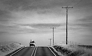 A loaded vehicle comes into view over a crest in the road in rural Klickitat County, WA, USA (monochrome high contrast grainy image)