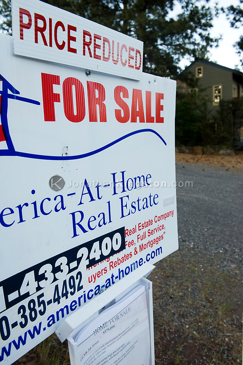 """A """"price reduced"""" """"for sale"""" sign in front of a house in Bend, Oregon."""