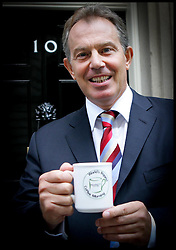 The British Prime Minister Tony Blair holds a  cup to help launch the world's biggest Coffee Morning PA Photo