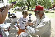 """6/4/2020 Jackson MS. A group of young protestors age 5 to 12 yrs old gathered outside the Old Mississippi State Capitol to protest the brutal murder of another African American man, George Floyd at the knees and hands of 4 former Minneapolis Minnesota police officers. They then marched past the Governors mansion and into Smith park where they met civil rights icon James Meredith by accident. Meredith then spoke to them about his March Against Fear and showed 5 yr. old called Herrington where he was shot. <br /> <br />  Civil right icon and Mississippi native son James Meredith sat on a park bench in downtown Jackson Mississippi and spoke with a group of kids wearing Black Lives Matter T-shirts and carrying signs that called for the end of White Supremacy. The kids and their guardians were protesting outside the old Capitol the group then marched past the Governors mansion into the park and met James Meredith. The group of young adults and their guardians were demonstrating in response to the brutal murder of George Floyd. This Saturday June 6th marks the 54th Anniversary of Meredith's March Against Fear. Meredith said """" Mississippi is the center of the universe, and if change is gonna happen it will start here first."""" He believes Mississippi is the most important and powerful word in the English language.<br /> Meredith was shot on the second day of his march by Aubrey James Norvell a member of the KKK. Norvell would later be the first white man convicted of shooting an African American. Photo© Suzi Altman"""