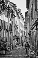 Black and white view of a narrow street, and colorful historic buildings, Old Annecy, France.