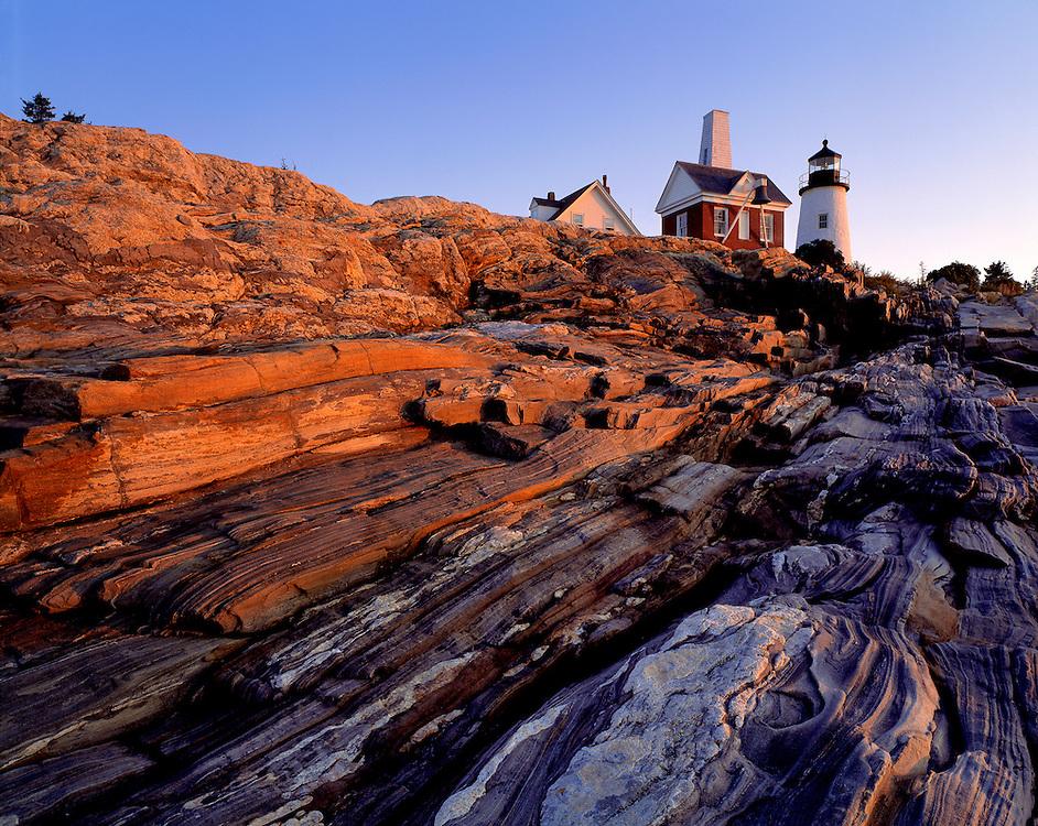 Pink sunrise light warms the rocks below Pemaquid Light, Lincoln Co., Maine.