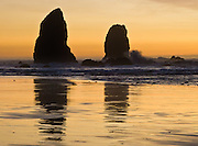 The pounding Pacific Ocean eroded sea stack rocks from bluffs at Cannon Beach, Oregon, USA. At dusk the sky glows yellow orange.