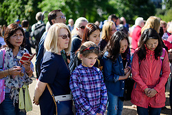 © Licensed to London News Pictures. 31/08/2017. London, UK. Members of the public look at flowers and tributes left at the gates to Kensington Palace in London on the 20th anniversary of the death of Diana, Princess of Wales. Princess Diana was fatally injured in a car crash along with her companion Dodi Fayed, while the couple were being driven through the Pont de l'Alma tunnel in Paris on 31 August 1997. Photo credit: Ben Cawthra/LNP