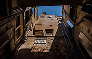 View of palazzo architecture from a small interior courtyard, looking up at the building and blue sky
