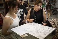 Un gruppo di pellegrine sceglie il tatuaggio da le dozzine di disegni proposti da Wassim