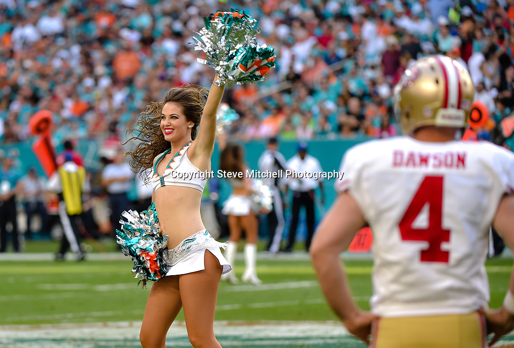 Nov 27, 2016; Miami Gardens, FL, USA; Miami Dolphins cheerleader performs in front of San Francisco 49ers kicker Phil Dawson (right) during the second half at Hard Rock Stadium. The Dolphins won 31-24. Mandatory Credit: Steve Mitchell-USA TODAY Sports