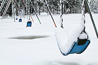 Snow covered swings in a playground park
