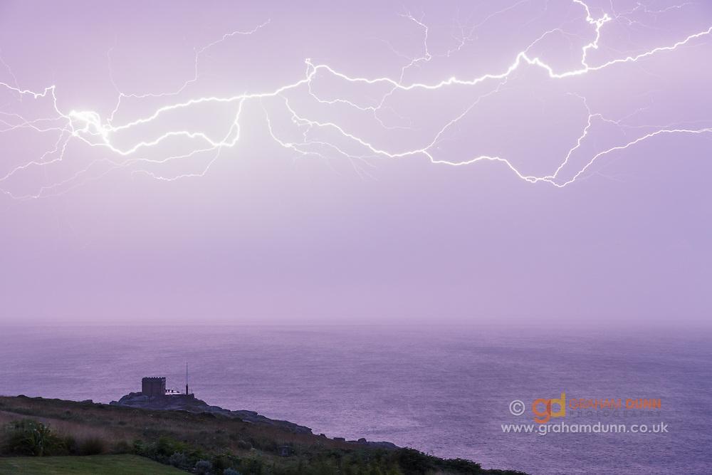 A dramatic lightning bolt over Mayon Lookout, an old coastguard station situated above Mayon Cliff, Sennen Cove - 1 mile north of Land's End in Cornwall. Numerous lightening strikes lit up the night sky during this spectacular and prolonged display as a dramatic electrical storm passed over Cornwall, England, UK on 17th July 2014.