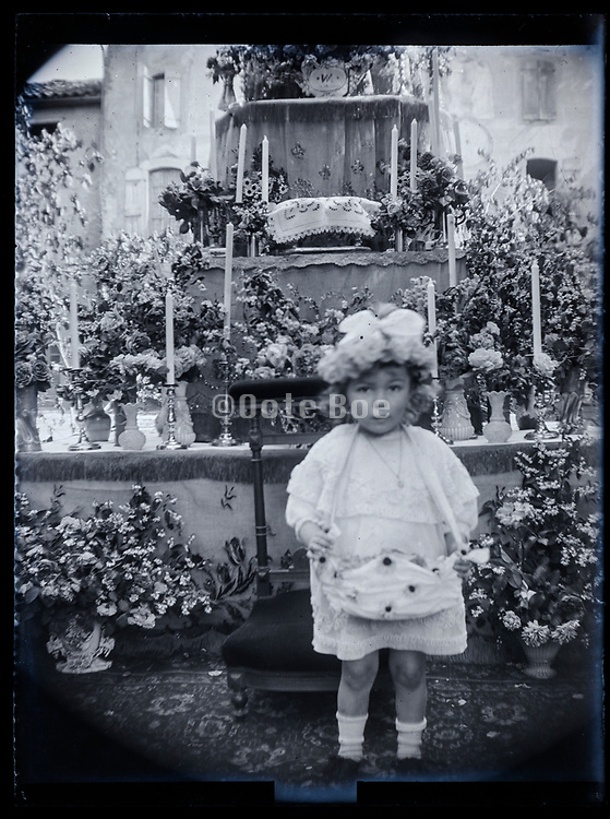little toddler girl standing by an decorated memorial  altar France 1923