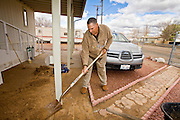 24 JANUARY 2010 -- WENDEN, AZ:  Jesus Pena cleans the yard of the Mesecher home in Wenden. Wenden was slammed by its second 100 year flood in 10 years on Thursday night when water raced through Centennial Wash and into the small town in La Paz County west of Phoenix. Most of the town's residents were evacuated to Red Cross shelters in Salome, about 5 miles west of Wenden.   PHOTO BY JACK KURTZ