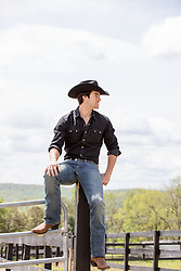 cowboy sitting on a fence post on a ranch