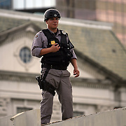 A Police officer watches from a rooftop as a protest parade approaches  during the Republican National Convention in Tampa, Fla. on Wednesday, August 29, 2012. (AP Photo/Alex Menendez)