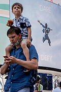 An image of a leaping figure from a Piccadilly Circus Calvin Klein ad whose slogan is Dare to Defy, and a man with a child on his shoulders on Covid Freedom Day. This date is what Prime Minister Boris Johnsons UK government has set as the end of strict Covid pandemic social distancing conditions with the end of mandatory face coverings in shops and public transport, on 19th July 2021, in London, England.