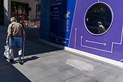 A elderly man with a poorly leg walks slowly past past a purple hoarding that screens off refurburshment works in the West End's Leicester Square, on 16th July 2021, in London, England.