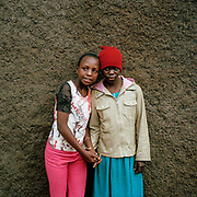 Sarah  10yrs, with Lucy 13 yrs (left) at the hostel where they live. The girls are good friends, and Lucy is like a member of the family to Sarah's mother. The block is typical; 20 families  live in one room houses paying 500 -1000 Kenyan shillings a month( £4-£8). The adults are separated from the children by a curtain .  They share a latrine and standpipe .