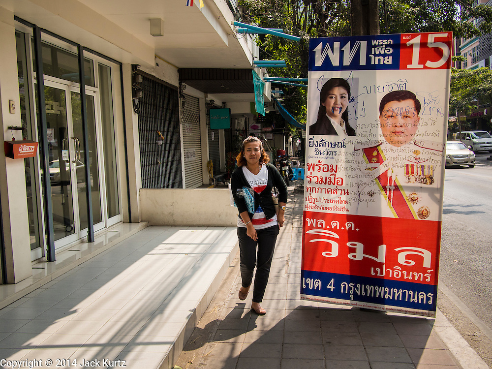 29 JANUARY 2014 - BANGKOK, THAILAND: A person walks past a defaced campaign sign for the ruling Pheu Thai party on Soi 63 Sukhumvit (Ekkamai) in Bangkok.  Thais are supposed to vote Sunday, February 2 in a controversial national election. Anti-government protestors have vowed to disrupt the election. One person was killed and several injured in election related violence during early voting on Sunday Jan. 25. The ruling Pheu Thai party is widely expected to win the election, which is being boycotted by the Democrats and opposition parties.      PHOTO BY JACK KURTZ