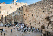 Jewish men pray at Kotel, as seen from the ramp where foreigners can access the Al-Aqsa Mosque and Temple Mount complex. On the bottom right the 9 branches version of the menorah (chanukiah)  erected in the men's section of the Western Wall in occasion of Hanukkah, the festival of lights.