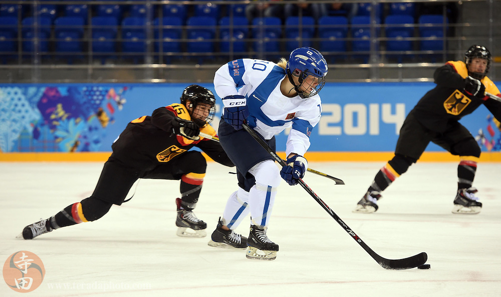 Feb 16, 2014; Sochi, RUSSIA; Finland forward Linda Valimaki (10) skates with the puck past Germany defenseman Andrea Lanzl (15) in the women's ice hockey classifications round during the Sochi 2014 Olympic Winter Games at Shayba Arena.