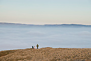A family enjoy the view from the summit of Mam Tor, Peak District