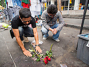 24 FEBRUARY 2014 - BANGKOK, THAILAND: Mourners leave flowers and pray at the spot where three people were killed in a grenade attack on anti-government protestors in the Ratchaprasong district in Bangkok. At least four people, three of them children, were killed in political violence over the weekend in Thailand. One in Trat province, near the Cambodian border, and three in Bangkok, at the Ratchaprasong protest site. At the Ratchaprasong site a grenade was fired into a crowd killing a child and an adult. A second child, injured in the blast, died overnight in a Bangkok hospital.  PHOTO BY JACK KURTZ