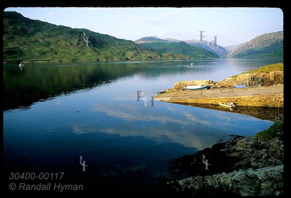 Boat ramp reflects in calm blue waters of Loch Glendhu at sunset along northwest coast; Kylesku. Scotland