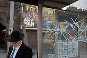 A Jewish gentleman, bus stop graffiti and an ad for the new Aardman Animations new release Early Man, on 30th January 2018, in the south London borough of Southwark, England.