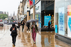 Edinburgh, Scotland, UK. 29 June, 2020. Many shops which have door access to the street are allowed to open for business in Scotland today. Despite cool temperatures, high winds and often heavy rain, some shops had queues outside in the morning. Tourist shops on the Royal Mile remained closed however, due to a lack of tourists,  and streets in the Old Town remained empty. Pictured; shoppers brave the rain on Princes Street.  Iain Masterton/Alamy Live News