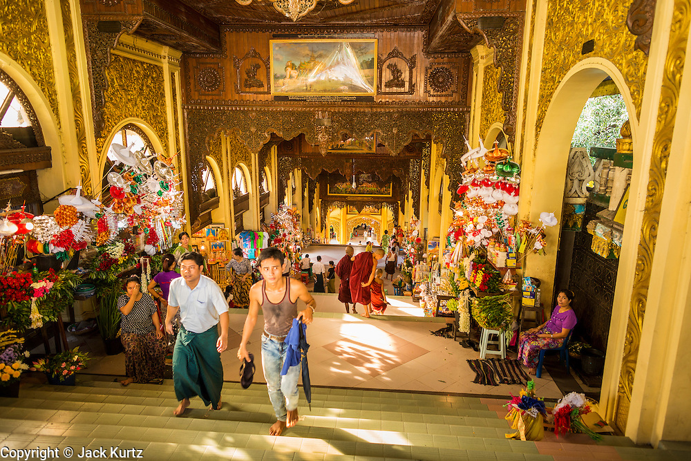 15 JUNE 2013 - YANGON, MYANMAR:  The north stairway into Shwedagon Pagoda. The Shwedagon Pagoda is officially known as Shwedagon Zedi Daw and is also called the Great Dagon Pagoda or the Golden Pagoda. It is a 99 metres (325ft) tall pagoda and stupa located in Yangon, Burma. The pagoda lies to the west of on Singuttara Hill, and dominates the skyline of the city. It is the most sacred Buddhist pagoda in Myanmar and contains relics of the past four Buddhas enshrined: the staff of Kakusandha, the water filter of Koṇāgamana, a piece of the robe of Kassapa and eight strands of hair fromGautama, the historical Buddha. The pagoda was built between the 6th and 10th centuries by the Mon people, who used to dominate the area around what is now Yangon (Rangoon). The pagoda has been renovated numerous times through the centuries. Millions of Burmese and tens of thousands of tourists visit the pagoda every year, which is the most visited site in Yangon.  PHOTO BY JACK KURTZ